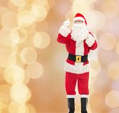 christmas, holidays, gesture and people concept - man in costume of santa claus with bag pointing finger up over beige lights background