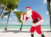 christmas, holidays and people concept - man in costume of santa claus running with gift box over tropical beach background