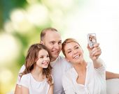 family, technology, ecology and people concept - smiling mother, father and little girl making selfie with camera over green background