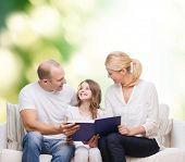 family, childhood, ecology and people - smiling mother, father and little girl reading book over green background