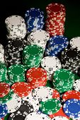gambling, fortune, game and entertainment concept - close up of casino chips on green table surface