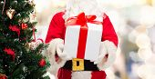 christmas, holidays and people concept - close up of santa claus with gift box and tree over lights background