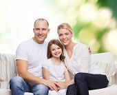 family, childhood, ecology and people concept - smiling mother, father and little girl over green background