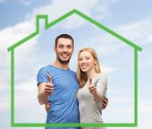 love, home, people, gesture and family concept - smiling couple hugging and showing thumbs up over green house and blue sky with clouds background