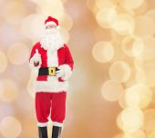 christmas, holidays, gesture and people concept- man in costume of santa claus showing thumbs up over beige lights background