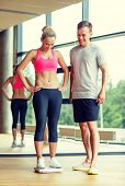 sport, fitness, lifestyle and people concept - smiling man and woman with scales in gym