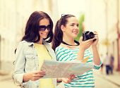 tourism, travel, leisure, holidays and friendship concept - two smiling teenage girls with map and camera outdoors