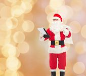 christmas, holidays and people concept - man in costume of santa claus with notepad and bag over beige lights background