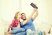 home, technology and relationships concept - smiling couple with tablet pc computer at home