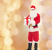 christmas, holidays and people concept - man in costume of santa claus with gift box over beige lights background