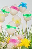 Easter eggs with multicolored ribbons on wooden sticks and green grass