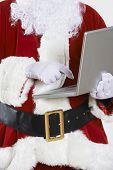 Santa Claus Using Laptop On White Background