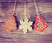 Gingerbread cookie hanging over a wooden background in a christmas theme toned with a retro vintage instagram filter effect