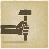 working symbol hand with hammer old background