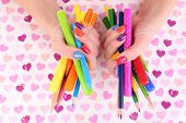 Multicolor female manicure with markers and pencils on bright background