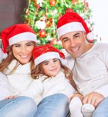 Portrait of happy parents with cute little daughter wearing red Santa hat sitting near beautiful Christmas tree and celebrating religious holiday