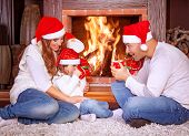 Happy family by fireplace, parents with baby girl wearing Santa Claus hats, sitting relaxed in ski resort chalet and drinking hot tea, joyful winter vacation, people traveling on Christmas holidays