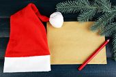 Santa red hat with branch of fir-tree, sheet of paper and pencil on color wooden background