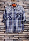 Male shirt on hanger on bricks wall background
