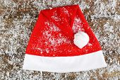 Santa red hat with snowflakes on wooden background