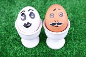 Pair of eggs in egg cups on green background