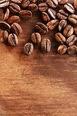 Coffee beans on wooden background, close-up