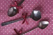 Metal spoons on pink polka dot fabric background