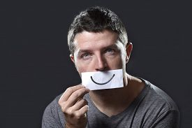 stock photo of depressed  - young depressed man lost in sadness and sorrow holding paper with smiley on his mouth as society forcing him to hide his pain in depression and lost of hope concept - JPG