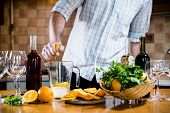 picture of sangria  - The man squeezes orange juice in a decanter for the preparation of sangria for home party - JPG