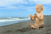 foto of tropical food  - After playing on the sea black sand beach little cute girl picnics of natural vegetarian food  - JPG