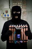 image of time-bomb  - Terrorist in black holding time bomb in warehouse - JPG