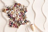 stock photo of calcite  - Artistic map of France from colorful waterworn pebbles arranged on decorative white sand with a pattern of wavy lines with Corsica island formed by a wine bottle cork copy space in a conceptual image - JPG
