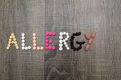 foto of allergy  - The word allergy written with pills on a wooden background - JPG