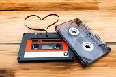 stock photo of heart sounds  - Vintage audio cassette with loose tape shaping one heart on a wooden background - JPG