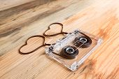 picture of heart sounds  - Vintage audio cassette with loose tape shaping two hearts on a wooden background - JPG