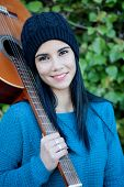 picture of guitarists  - Pretty guitarist with his guitar on his shoulder in the park - JPG