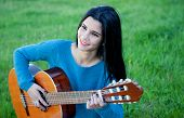 image of guitarists  - Pretty guitarist playing the guitar sitting on the grass - JPG