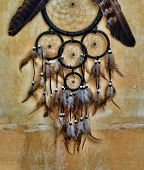 stock photo of dream-catcher  - dream catcher with eagle and raven feathers on orange structure wall - JPG