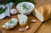 pic of curd  - Slices of baguette with cottage cheese parsley garlic on a cutting board - JPG