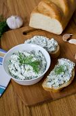 stock photo of curd  - Slices of baguette with cottage cheese parsley garlic on a cutting board - JPG
