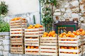 stock photo of crop  - fresh crop of oranges in wooden boxes on a street market in Taormina town Sicily Italy in spring - JPG