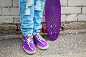 stock photo of snickers  - Teenager in jeans and gumshoes stands with skateboard near gray urban brick wall - JPG