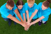 stock photo of joining hands  - People joining their hands  on green grass  - JPG