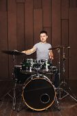 picture of drum-kit  - Handsome guy behind the drum kit on a brown background - JPG