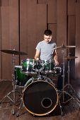 foto of drum-kit  - Handsome guy behind the drum kit on a brown background - JPG