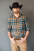 stock photo of cowboys  - Handsome young man wearing cowboy hat and looking at camera while standing against grey background - JPG