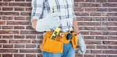 picture of pliers  - Technician with tool belt around waist holding pliers against red brick wall - JPG