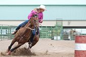 stock photo of barrel racing  - Beautiful young woman riding a horse in a barrel racing competition in a rodeo - JPG