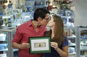 foto of wifes  - People running small family business with asian shop owner and caucasian wife in computer store showing their first dollar to the camera and kissing - JPG