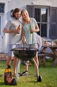 image of tong  - Women helping boyfriend husband at outdoor garden barbecue with tongs and beer - JPG
